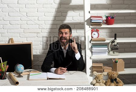 Professor with happy face having idea. Teacher and school supplies in classroom. Man with beard on white brick wall background. Education and knowledge concept.