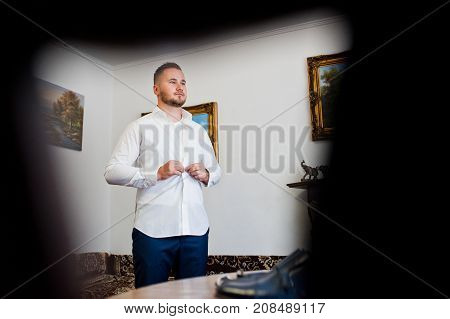 Portrait Of A Handsome Groom Dressing Up In Spacious Luxurious Room And Getting Ready For His Huge W