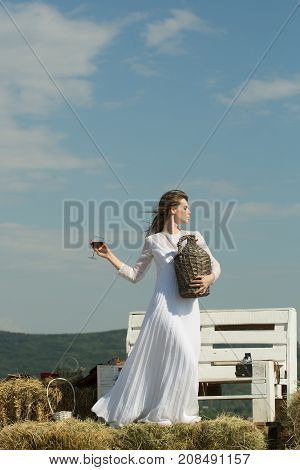 Girl in white dress posing on blue sky. Woman with glass of red wine and wicker bottle. Winery tour concept. Summer vacation holidays and celebration. Model with alcohol drink on sunny day.