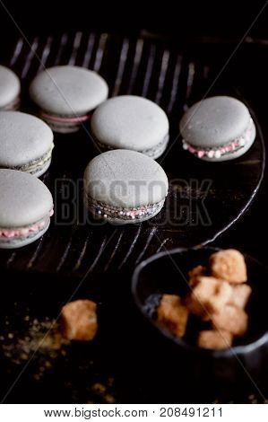 Dark monochrome photography. Grey cakes macaroons on the dark surface of the table, next to a spoon and sugar bowl with brown sugar.