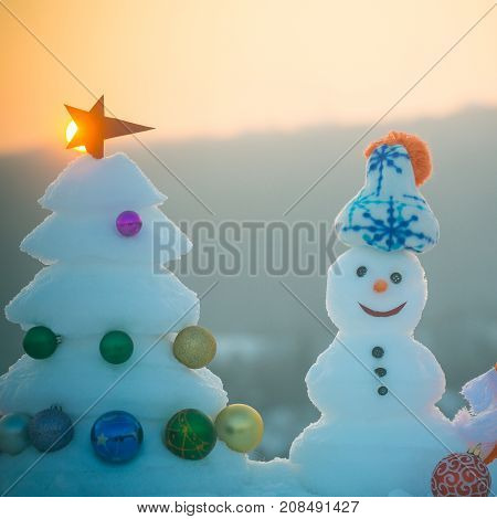 Snowman With Smiley Faces In Hat On Evening Landscape