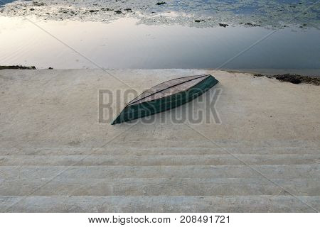 An inverted boat on a concrete embankment on the shore of a mountain lake at sunset.