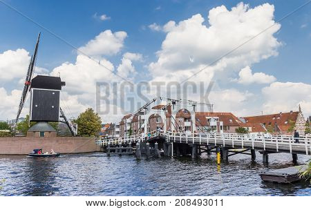 LEIDEN, NETHERLANDS - SEPTEMBER 03, 2017: White bridge and historic windmill at a canal in Leiden Holland