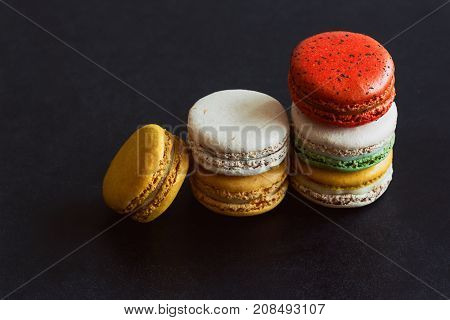 Close up colorful French macaron or Italian macaron. Homemade delicious macaron stack on granite table with copy space for background or wallpaper. French dessert for served with tea or coffee. Macarons background concept on granite table.