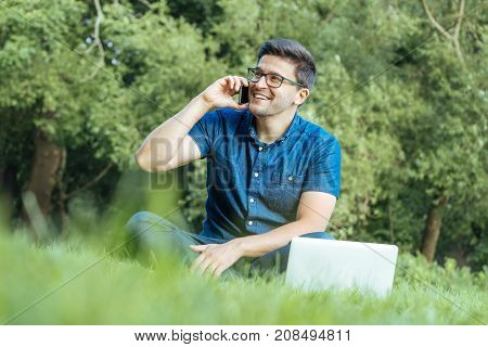 Young Man Using Smartphone While Sitting On Grass
