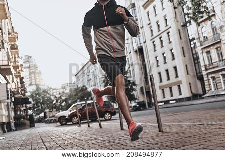On the way to great shape. Close up of young man in sport clothing running along the city street