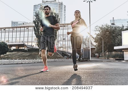 Making effort. Full length of young couple in sport clothing running through the city street together