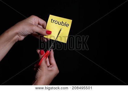 Photo on a dark background. Yellow sticker. Steel scissors.
