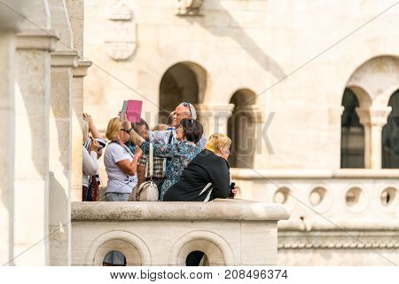 A balcony viewpoint in Budapest near Matthias Church with a small group of people looking at the view and taking selfie pictures. Budapest Hungary - September 27 2017: Daytime side view of a small group of caucasian male and females standing at a viewpoin