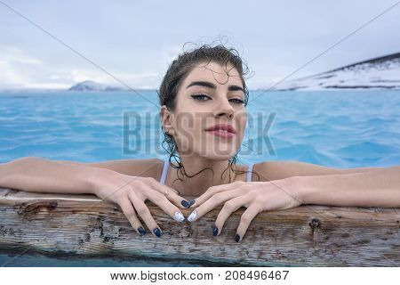 Happy girl in a white swimsuit holds a wooden crossbeam in the geothermal pool on the background of snow mountains and cloudy sky outdoors in Iceland. She looks into the camera with parted lips.