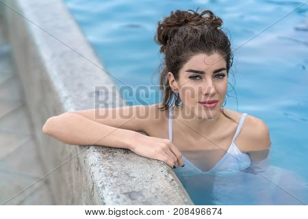 Smiling girl in a white swimsuit leans on the edge of the geothermal pool outdoors in Iceland. She looks into the camera. Closeup. Horizontal.