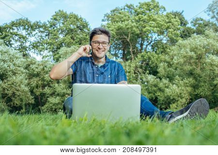 Young man with laptop using smartphone while sitting on grass