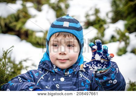 Winter Portrait Of Kid Boy In Colorful Clothes, Outdoors During Snowfall. Active Outoors Leisure Wit
