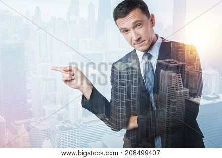 Right direction. Reliable pleasant attentive man pointing to the right while standing and looking straight