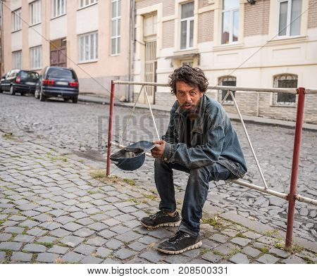 Homeless man on the street of the city. Senior beggar