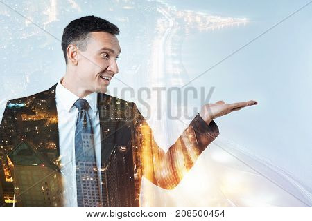 Check it. Enthusiastic experienced clever businessman looking glad while showing the advantages of working in his company