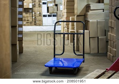 Warehouse with goods in boxes and trolleys for transportation of goods close-up.