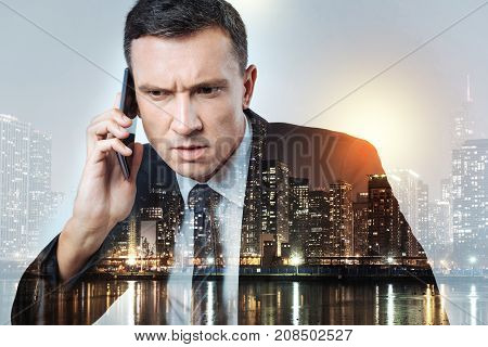 Unbelievable. Busy man in a black suit looking surprised and irritated while hearing unexpected new from his colleague on the phone