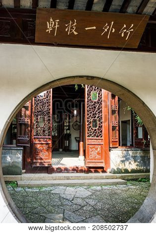 Suzhou, China - Nov 5, 2016: Master of Nets Garden (Wang Shi Yuan) - Moon gate doorway leading into a small residential courtyard designed in the classical Chinese architecture style, with some bamboo bush in front.