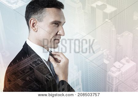Stylish tie. Pleasant elegant smiling man looking calm while wearing a tie