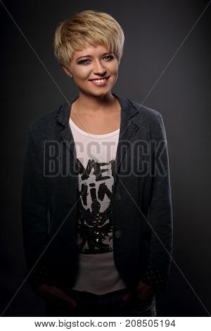 Happy Smiling Young Blond Woman With Short Bob Hair Style Looking In Grey Trendy Jacket On Dark Back