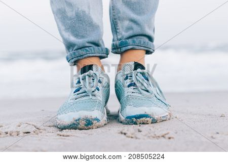 Female feet in wet jeans and sneakers on the beach close-up
