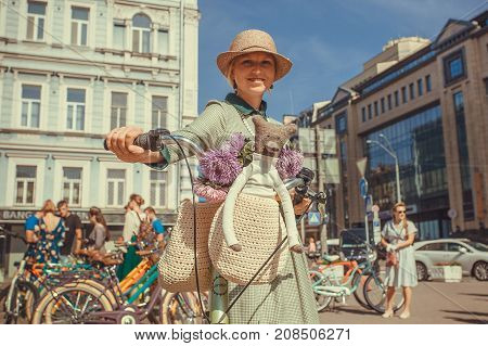 KYIV, UKRAINE - SEP 17, 2017: Cute woman with bicycle and teddybear going to vintage festival Retro Cruise on September 17, 2017. Kiev is the 8th most populous city in Europe