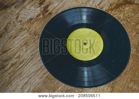 Vinyl disc on a wooden background, close view