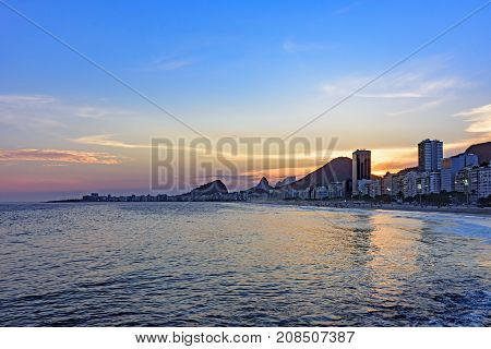 Leme and Copacabana beaches in Rio de Janeiro during sunset with its buildings and the mountains in the background