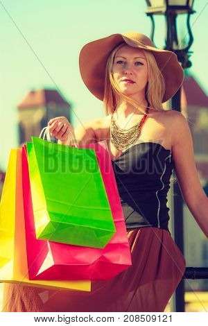 Spending money buying things concept. Fashionable woman resting after big shopping sitting on pole with bags in the old town wearing glamorous outfit and big sun hat poster
