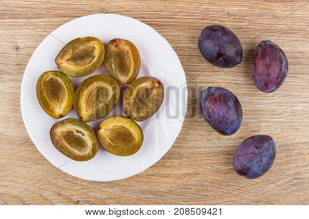 White Plate With Halves Of Plums And Whole Plums