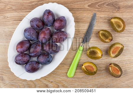 Ripe Plums In Oval Dish, Halves Of Plums And Knife