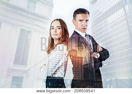 Reliable people. Strict elegant man looking concentrated while standing with his young cheerful colleague