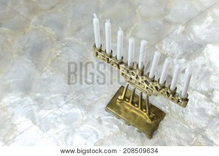 Small brass Hanukkah menorah on a soft white background, angled right