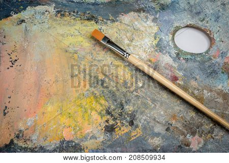 Oil paint of different colors on a palette and brushes