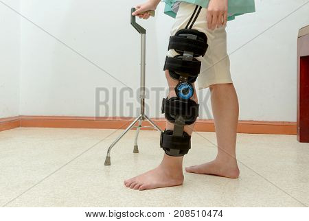 Woman Walking On Crutches, Wearing Knee Support In Rehab Center