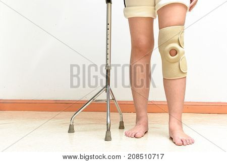 Woman walking on cane wearing knee support in rehab center