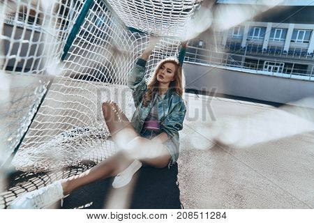 Trendy beauty. Attractive young woman in casual wear touching goal post while sitting outdoors
