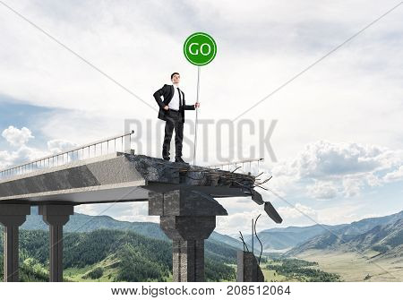 Confident businessman in suit holding green go sign while standing on broken bridge with skyscape and nature view on background. 3D rendering.