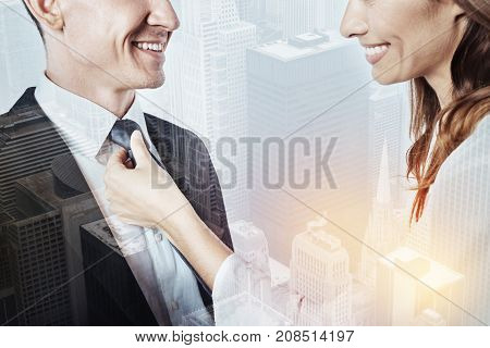 Loving wife. Kind cheerful smiling wife helping her beloved busy husband to knot a tie before going to work