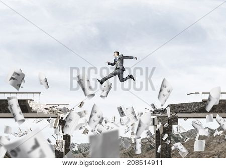 Businessman jumping over gap in bridge among flying papers as symbol of overcoming challenges. Skyscape and nature view on background. 3D rendering.