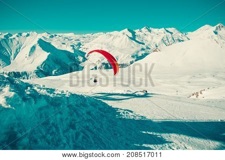 Paraglider tandem flying over Gudauri . Colorful parachute. Active lifestyle Extreme hobbies. Paragliding Georgia. Adventure travel. Winter mountain landscape. Fearlessness concept. Freedom. Toned