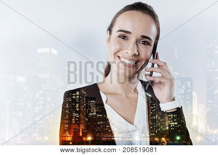 Nice conversation. Pleasant friendly smiling woman holding a smartphone near her left ear while having a nice conversation