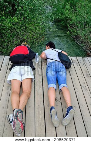 Two young women lie on a wooden bridge over a river