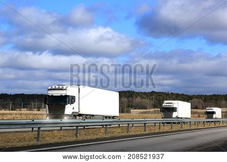 Three white semi trailer cargo trucks platoon on freeway at spring with blue sky and clouds background. Copy space top of image.