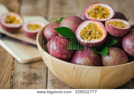 Passion fruit on wood bowl put on wood table in side view for background or wallpaper. Prepare passion fruit on cutting board for homemade dessert or cooking. Ripe passion fruit so sweet and sour. Fresh passion fruit background concept.