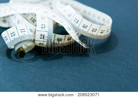 Close up tailor measuring tape on a black background. White measuring tape shallow dept of field.