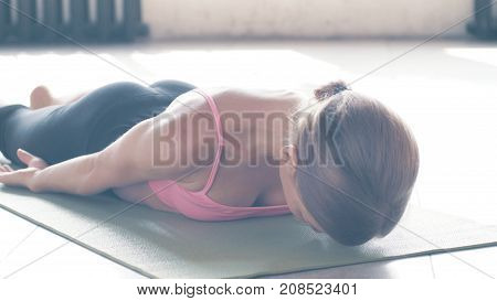 Exercises from yoga close-up, shows a beautiful girl in a pink top and black sports breeches. A yoga coach does exercises in a beautiful loft with masonry painted white and large windows to the floor through which the sun shines.