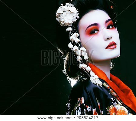 Young beautiful asian woman's portrait, geisha in kimono on black