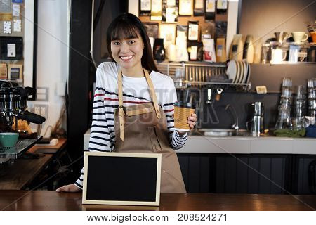 Portrait of smiling asian barista holding cup of coffee with blank chalkboard menu at counter in coffee shop. Cafe restaurant service food and drink industry concept.